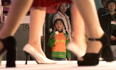A YOUNG GIRL ADMIRES MODELS WEARING THE LATEST CHINESE FASHIONS AT THE 10TH CHINA INTERNATIONAL ...