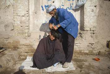 Afghan street barber cuts customer's hair at street corner in Herat