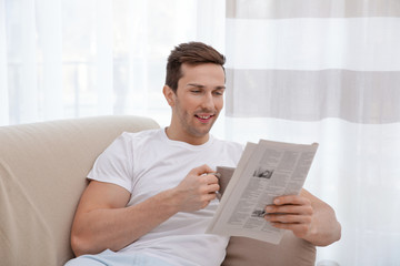 Young man resting on couch with newspaper and drinking tea in light room