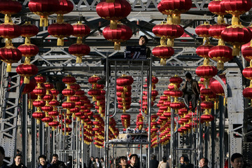A labourer prepares lanterns for the upcoming Lunar New Year at The Zhongshan Bridge in Lanzhou