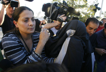 Lisa Nowak, with jacket over her head, is escorted to a car after leaving the Orange County Jail in Orlando, Florida