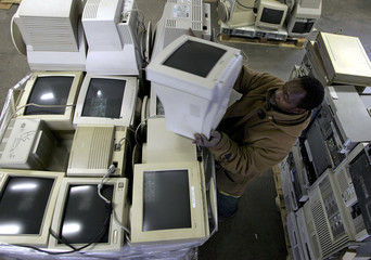 Worker of Ecomicro recycling company, lifts a used computer monitor in Bordeaux