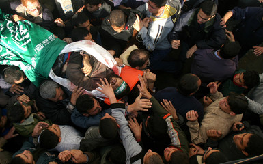 Palestinians carry the body of Hamas militant Mohammed Abu al-Ros during his funeral at al-Buraji ...