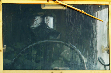 US SOLDIER IN GAS MASK SITS IN HIS VEHICLE DURING DRILL IN KUWAIT.