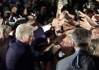 US PRESIDENT CLINTON MOBBED BY TROOPS AT CAMP ON OKINAWA.