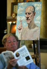 PRITIKIN READS IN FRONT OF HIS PAINTING OF BARE CHESTED PRINCE PHILIP.