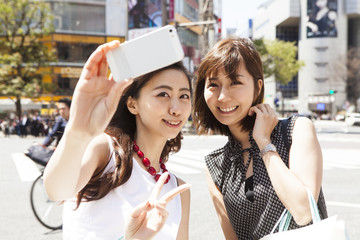 Two young ladies are shooting at the intersection of Shibuya