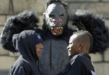 """IBF Bantamweight champion Joseph """"King Kong"""" Agbeko (R) and challenger Yohnny Perez face off in front of a man in a gorilla costume during a boxing news conference at the Treasure Island hotel-casino in Las Vegas"""