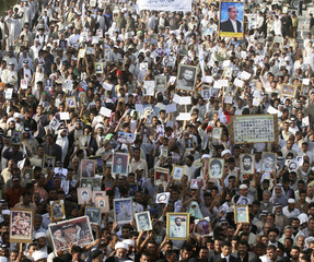 Demonstrators hold pictures of their missing and killed relatives during a protest in Najaf