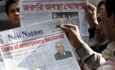 Residents read newspapers near a roadside stall in the capital Dhaka