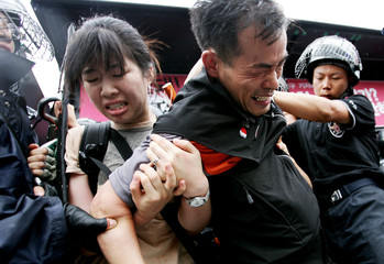 Riot policemen detain protesters at a rally in Seoul