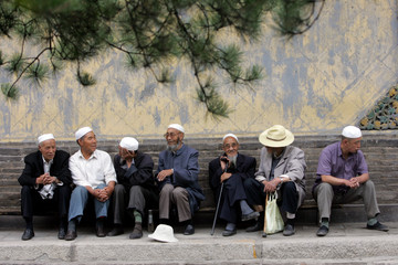 Muslim men from the Chinese Hui minority chat at the Dongguan Great Mosque in Xining