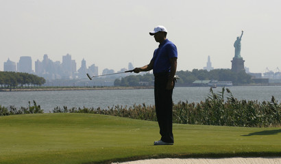 New York's lower Manhattan skyline and the Statue of Liberty are seen in the background as Tiger Woods of the U.S. lines up a putt