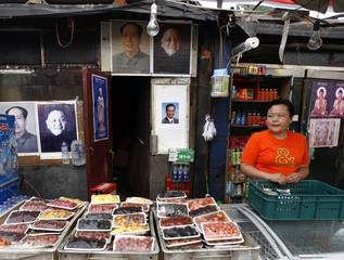 Yu stands in her dried fruit and nuts kiosk adorned with posters of former Chinese leaders Deng and Mao plus the current Premier Wen in Beijing