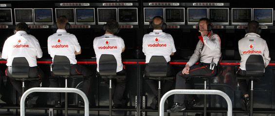 McLaren Formula One team members watch monitors in pits during practice session in Oyama