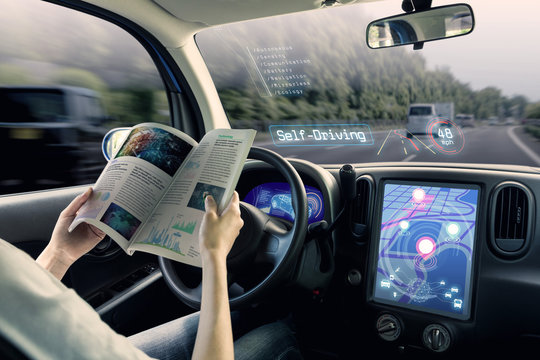 cockpit of autonomous car. a vehicle running self driving mode and a woman driver reading a book.