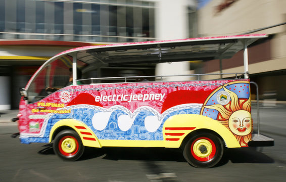 An e-jeepney, which is an electric-powered jeep runs past regular jeepney's, the country's most recognizable icon during its test run in a busy street of Makati's financial district in Manila