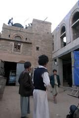 Boys stand outside the house raided by Yemeni forces in al-Ashraf village