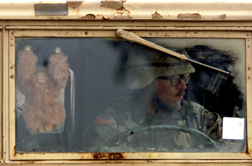 U.S. SOLDIER DRIVES TRUCK WITH A MONKEY MASCOT ON THE WINDSCREEN AT AMILITARY CAMP OUTSIDE BAQUBA IN IRAQ.