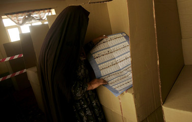 An Afghan woman searches for a candidate on a ballot during parliamentary elections in Kabul.