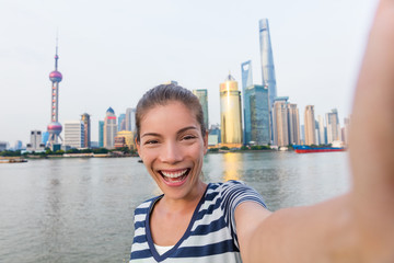 Happy Asian tourist woman taking selfie on The Bund. Smiling young lady holding smartphone camera to take a picture of herself in front of Shanghai's landmak, skyline of skycrapers in Pudong, China.
