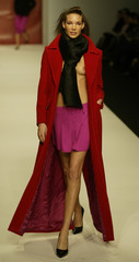 A MODEL WEARS A FLOWING RED COAT WITH PINK SKIRT AT PAUL COSTELLOE SHOWIN LONDON.