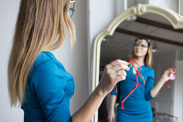 Ophthalmology concept - blonde young woman with red glasses near mirror
