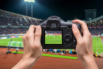 Hand holding the camera over blurred of action photographer taking photo at player in Abstract blurred photo of soccer stadium, sport background concept