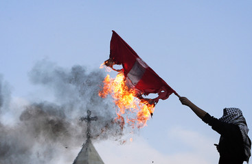 A masked Palestinian holds a burning Danish flag in front of the Church of Nativity in the West Bank city of Bethlehem