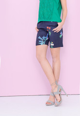 Woman long sexy legs wearing jeans shorts with floral on pink background