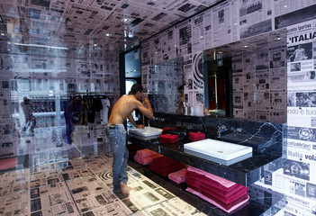 Footballer Andrea Vasa of Italy brushes his teeth in Dirk Bikkembergs fashion store in downtown Milan