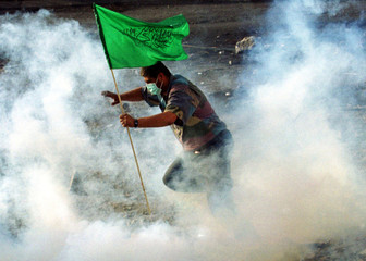 A Palestinian protester holding a Hamas flag runs through a cloud of tear gas fired by Israeli secur..