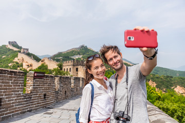 Happy couple tourists taking selfie picture at Great wall of china, top worldwide tourist destination. Young multiracial people using phone photography app for photos.