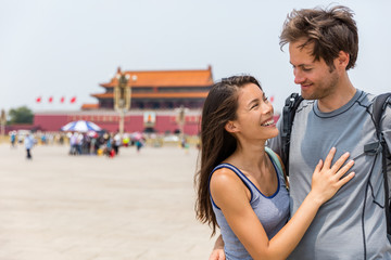 Wall Mural - Happy multiracial couple on summer holidays having fun laughing together in love on Tianamen Square, Beijing, china. Asia travel. Chinese woman, Caucasian man, multiethnic tourists.