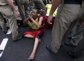 A Tibetan exile pleads to Indian police during a protest in New Delhi
