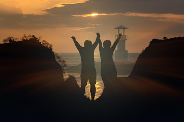 Silhouette of happy lover holding each other on Seascape at sunset with Lighthouse on the coast, valentine lover concept