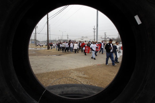 Legal US residents waiting for citizenship are pictured through a tire as they march to the Dallas US Citizenship and Immigration Services office to protest delays in the processing of their applications