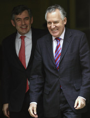 Britain's Chancellor of the Exchequer Brown and Northern Ireland Secretary Hain smile as they walk out of 11 Downing Street in central London