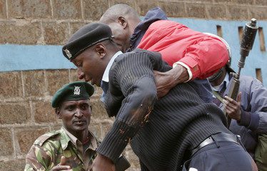 A wounded policeman is helped by colleagues during a protest after the vote counting was discontinued over poll violence in Kajiado