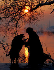 A Russian woman feeding dogs is silhouetted against the sunset over the Moskva River steaming in heavy frost in Moscow