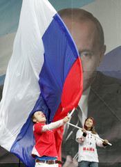 Russia's President Putin's supporters wave a state flag with the president's portrait in the background as they celebrate his 55th birthday in central Moscow