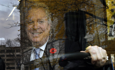 Quebec's Premier Jean Charest smiles as he sits behind the wheel of his campaign bus after he called an election in Quebec City