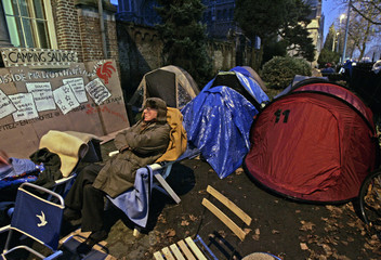 A man sits in front of tents placed by parents and used as shelters outside a Brussels school