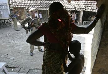 Villagers watch as paramilitary soldiers patrol Nandigram village