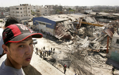 Palestinians inspect a destroyed depot following an Israeli air strike in Gaza