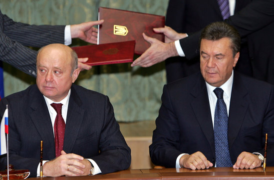 Ukraine's Prime Minister Yanukovich and his Russian counterpart Fradkov sit at the table as officials exchange documents in the background during the signing ceremony after negotiations in Kiev