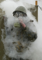 A SOLDIER IN GAS MASK LEAVES A TENT DURING EXERCISES IN NARO-FOMINSK.