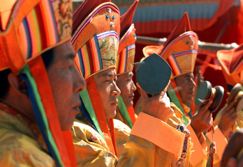 Tibetan lamas shake prayer drums on stage at the opening ceremony of the Shoton, a local festival in..