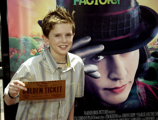 "Freddie Highmore poses with a ""golden ticket"" at the Los Angeles premiere of ""Charlie and the Chocolate ..."