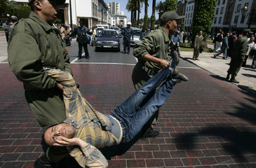 A protestor is carried away by security personnel during a protest in Rabat